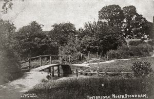 View of footbridge looking southwest, with glimpse of Cottages Nos. 39-44